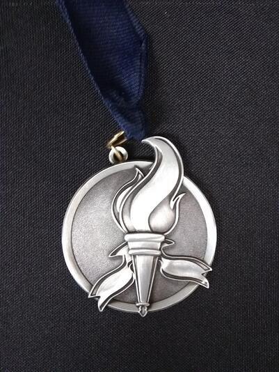 The Class 5 medal featuring a blazing torch.